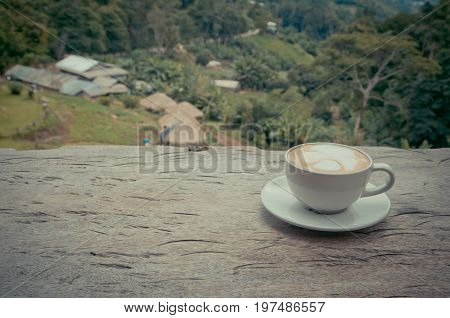 hot coffee on wood table with mountain view