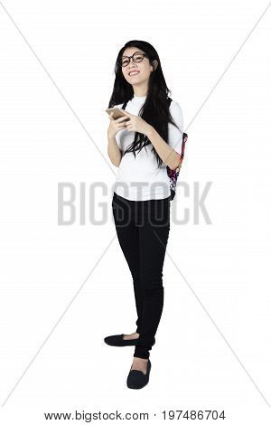 Full length of happy female high school student standing in the studio while using a smartphone. Isolated on white background