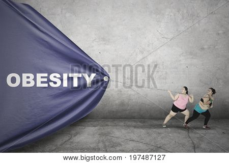 Two obese young women pulling a big banner with Obesity text and wearing sportswear