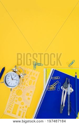 back to school styed scene with blue and yellow school supplies on yellow background