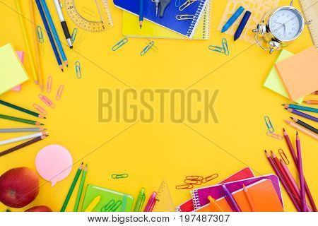 back to school or office styed scene with multicolored school supplies on yellow