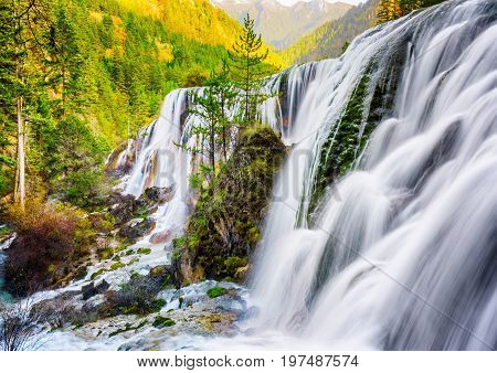 The Pearl Shoals Waterfall Among Wooded Mountains At Sunset