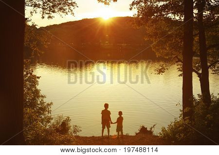 Children at the water watching the setting sun. Two boys holding hands standing on the shore. Back view. Copy space for your text