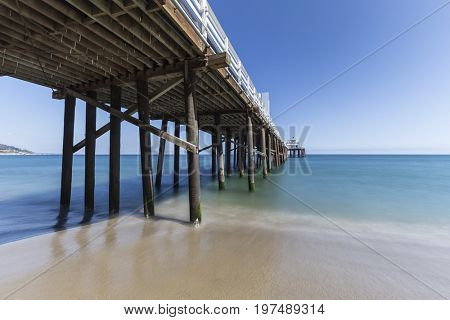 Malibu Pier Beach with motion blur pacific ocean water near Los Angeles in Southern California.