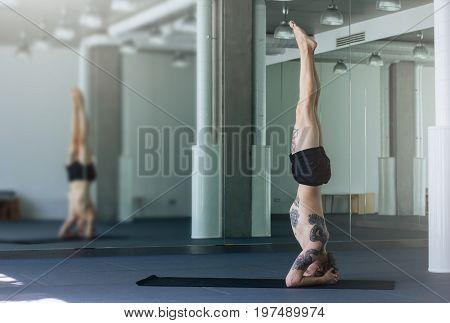 Handsome Tattooed Man Practicing Yoga. Young Male Teacher Taking Headstand Pose / Sirsasana Asana In