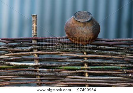 An Old Pitcher On A Wooden Fence..