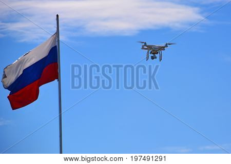 Flying drone with camera. Drone with digital camera flying over a Russia flag