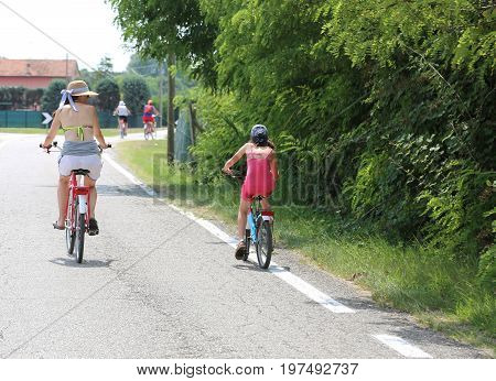 Family With Mom And Young Daughter Pedal On The Paved Road