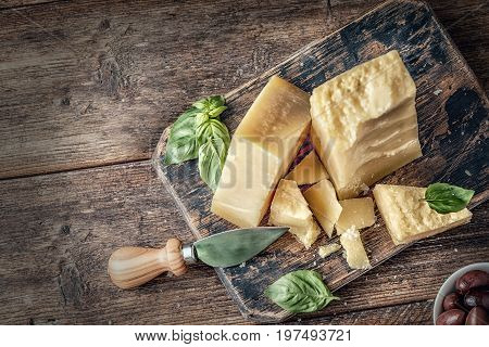 Parmesan cheese on wooden board with basil leaves. Pieces of cheese parmesan on wooden table and cheese knife. Top view.