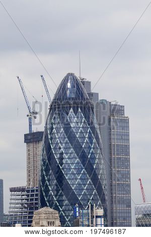 LONDON UNITED KINGDOM - JUNE 22 2017: London's primary financial district the City of London commercial skyscraper Gherkin Millennium Tower. It was opened in April 2004 with 41 storeys it is 180 metres tall.