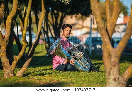 Jazz musician with the tuba sitting on the grass in the Park.