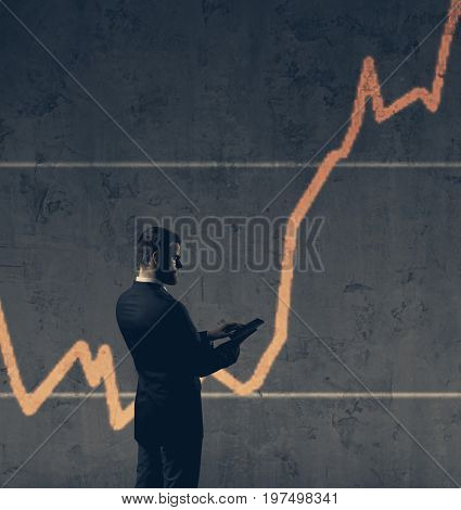 Businessman with computer tablet standing over column diagram background. Business, crisis, default concept.
