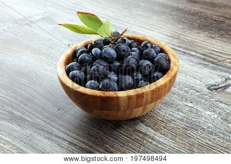 Freshly Picked Blueberries In Wooden Bowl. Juicy And Fresh Blueberries With Green Leaves On Rustic T