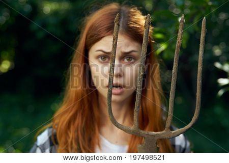 Young beautiful woman holds a pitchfork in the garden, gardener, summer.