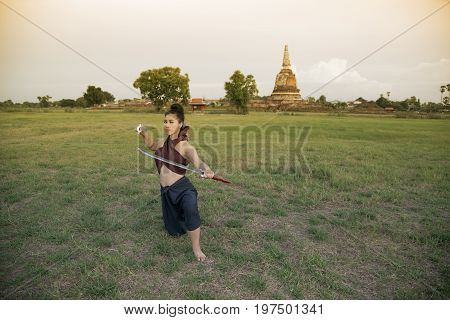 Pretty Asian woman posing in Thai ancient warriors at Wat Chang ancient abandoned temple in Ayutthaya Historical Park ,Thailand.