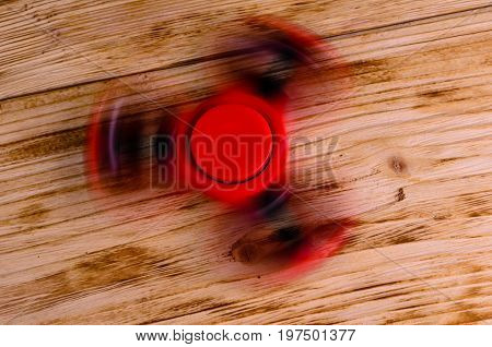 Red Fidget Spinner Rotates On Wooden Desk