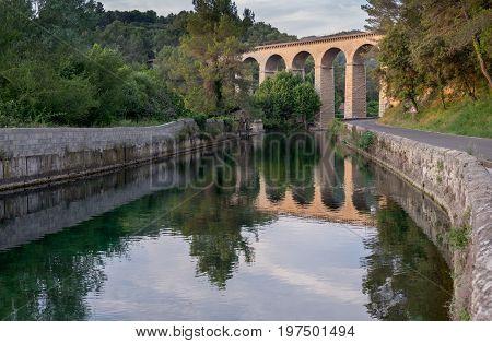 Ancient Galas Aqueduct at Fontaine-de-Vaucluse village. Sunset time. Provence. France