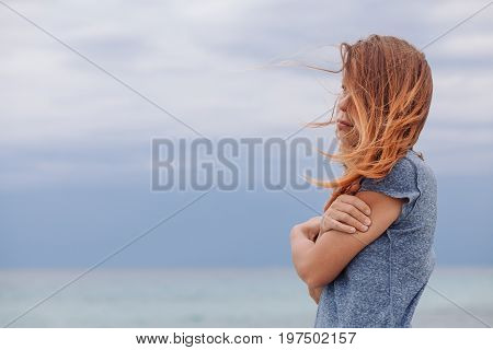 Woman alone and depressed at seaside on a cloudy weather