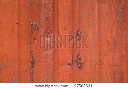 Old metal wall. Old metal background.  Old metal wall of the garage painted red. Red metal wall. Red metal texture.