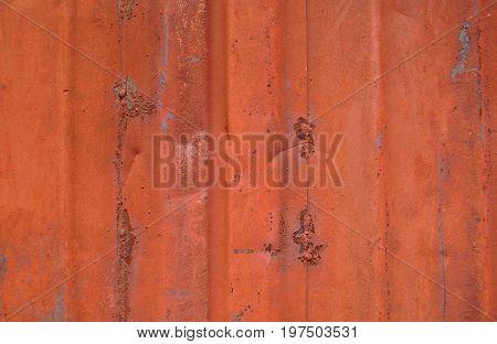 Old metal wall. Old metal background.  Old metal wall of the garage painted red. Red metal wall. Red metal texture.
