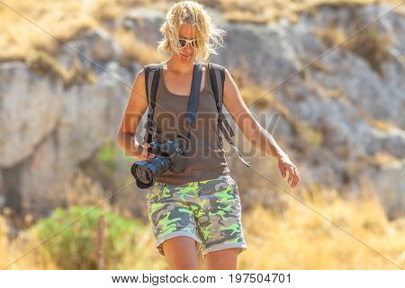 Caucasian young hiker during a trekking on a blurred landscape. Traveler woman photographer with professional camera outdoor. Female photographer walking in nature. Adventure and leisure concept.