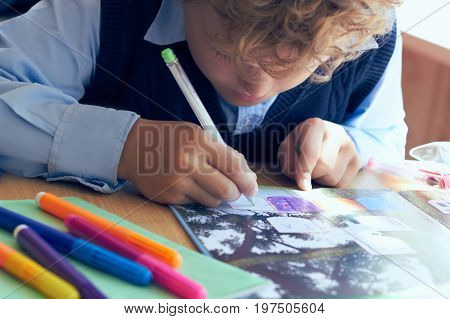 Little child writing with colorful pencils at school. Elementary school and education concept.