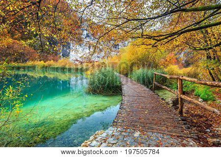 Wonderful touristic wooden pathway in the colorful deep forest with clean lake Plitvice National Park Croatia Europe