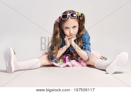 Fashion unhappy pensive red-haired girl with goggles on her head sitting on the floor dream. Studio photo on light coloured background. Birthday holiday