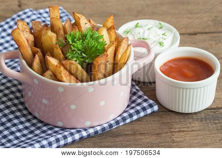 Homemade french fries serve with ketchup and sour cream or mayonnaise. Golden brown crispy french fries sprinkle with salt and oregano on bowl for snack or appetizer. French fries on wood table. Delicious french fries ready to served.