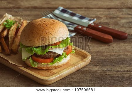 Homemade hamburger on wood plate with french fries. Delicious sandwich hamburger with meat or pork ham cheese and fresh vegetable. Hamburger or sandwich is the popular fast food for brunch or lunch. Cheese burger ready to served on table.