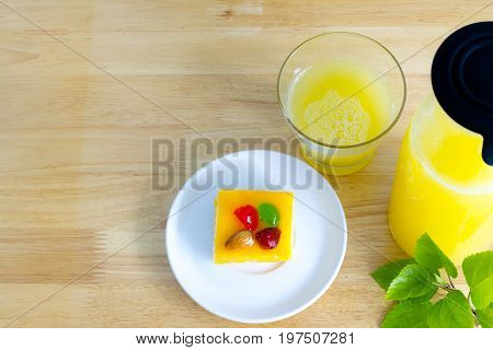 Mini cake Pineapple juice and green leaves placed on wooden table.