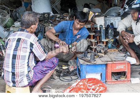 Bali Indonesia - July 30 2013. Unidentified men reparing motors engine on the floor poor garage owner doing mechanic
