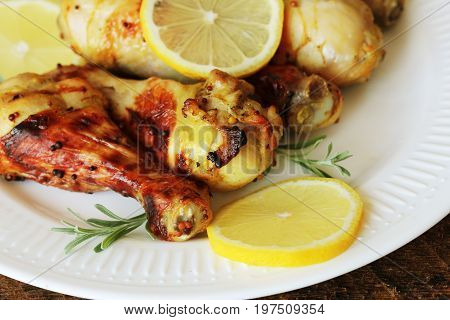 Grilled chicken legs with mustard on wooden table served on white plate with rosemary. BBQ dinner background .