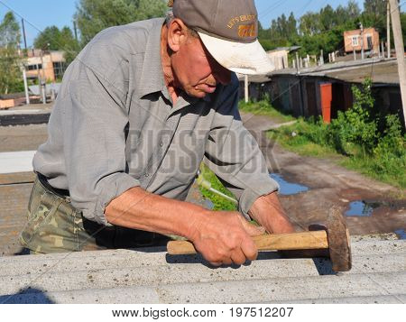 KYIV UKRAINE - AUGUST 16, 2017: Roofer repair asbestos roof with hammer. Old contractor roofing construction.