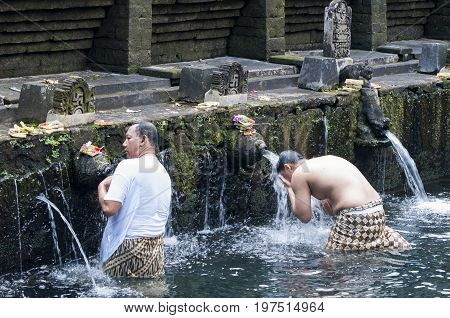 Bali Indonesia - July 30 2013. Holy Spring Water Tirta Empul Hindu Temple unidentified people have a bath in the temple under the waterfalls to be cleansed.