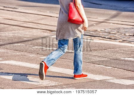 road crossing with woman pedestrian feet on sunny spring day