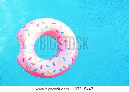 Inflatable swim ring in shape of donut floating in pool