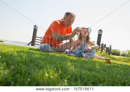 Joyful Father And His Little Serious Daughter Are Blowing Bubbles