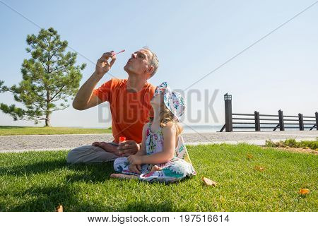 Serious Father And His Little Daughter Together Inflate Bubbles