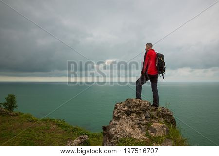 Man Traveler Stands On A Cliff In Front Of The Sea