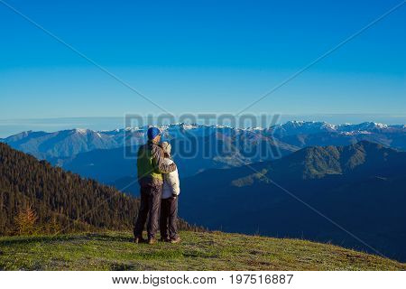 Couple Of Travelers, Hugging, Is Admiring The Dawn In The Mountains