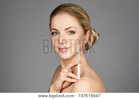 beautiful young woman holding syringe with collagen treatment injection. beauty shot on grey background. copy space.