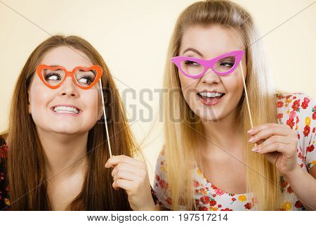 Two Happy Women Holding Fake Eyeglasses On Stick