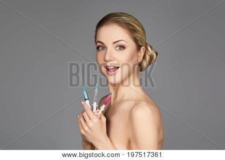 beautiful young woman holding three syringes with collagen treatment injection. beauty shot on grey background. copy space.