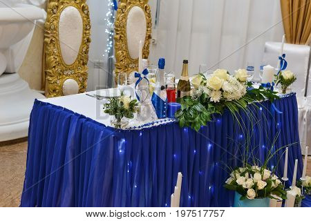 Wedding table setting in restaurant: nametags, chairs, wine glass, cutlery, plates, flowers and decoration on tables