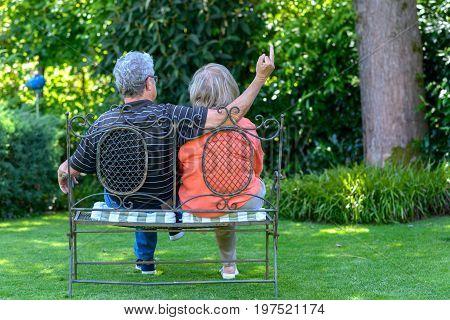 Senior Couple Sitting On A Garden Bench