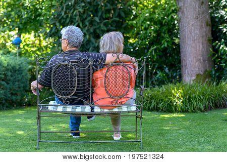 Elderly Couple Sitting In A Lush Green Garden