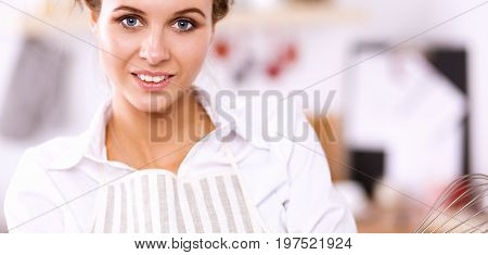 Woman with corolla standing in the kitchen .