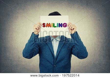 Businessman covering his face using a white paper with drawn smiling text inscription like a fake mask for hiding his real emotion from society. Isolated gray wall background.