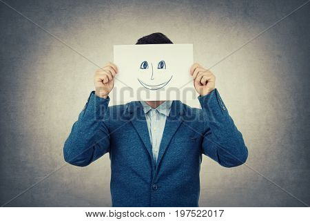 Businessman covering his face using a white paper with drawn smiling emoticon sketch like a fake mask for hiding his real emotion from society. Isolated gray wall background.